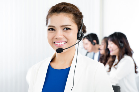 microphone headset: Smiling woman wearing microphone headset as an operator, telemarketer, call center and customer service staff Stock Photo