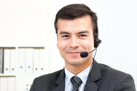 microphone headset: Smiling handsome businessman wearing microphone headset - telemarketing, operator, call center and customer service concepts Stock Photo