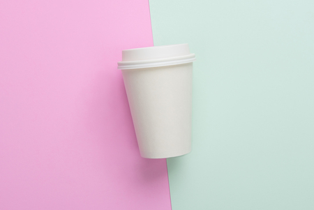 take out: Disposable takeaway (take out) coffee cup on light blue and pink background Stock Photo