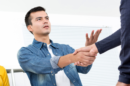 casual office: Handsome man wearing casual jean shirt making handshake in the office - soft and selective focus
