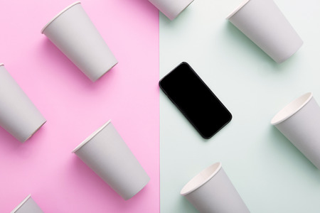 uniqueness: Mobile phone in group of white coffee cups - standing out, individuality and uniqueness concepts