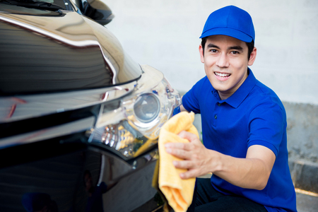 valeting: Young man polishing (cleaning) car with microfiber cloth - car detailing, valeting  and auto service concepts