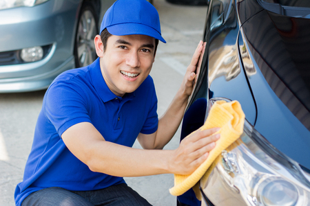 wash cloth: Young man polishing (cleaning) car with microfiber cloth - car detailing, valeting  and auto service concepts