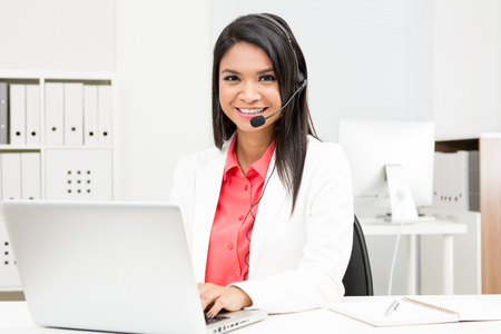 online service: Businesswoman wearing microphone headset using laptop computer in the office - operator, call center, telemarketing and customer service staff concepts