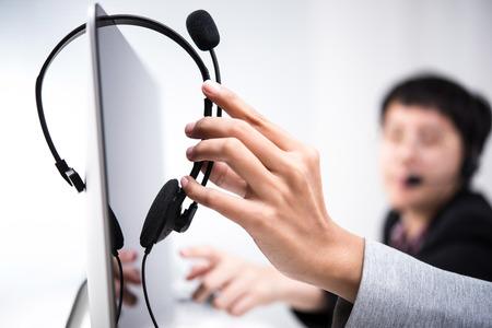 Hand picking up headphone that hanging on computer screen Stock Photo