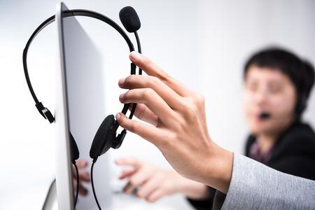 Hand picking up headphone that hanging on computer screen Reklamní fotografie