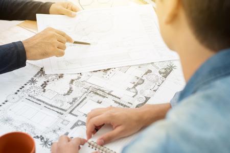 Architects (landscape designers) discussing blueprints
