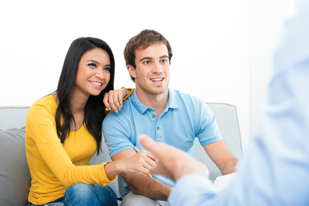 Young couple meeting with  consultant (or counselor, financial adviser, real estate agent etc.) Imagens - 63210322