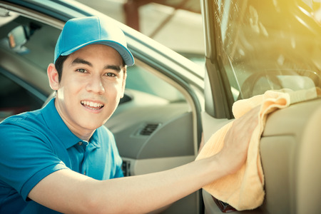 valeting: Smiling auto service staff cleaning car door - car detailing and valeting concept