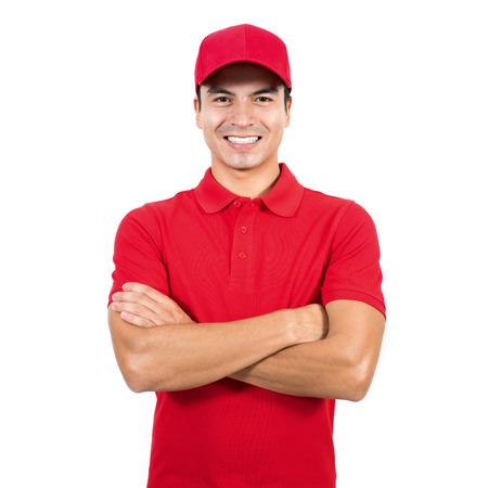 Lachende levering man in het rode uniform staat met arm gekruist - geïsoleerd op een witte achtergrond