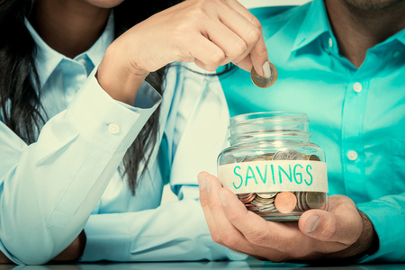 ahorros: Mano de la mujer que pone el dinero (monedas) en el frasco de vidrio AHORROS marcados en poder de un hombre