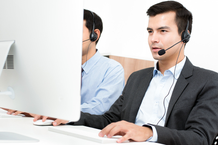 microphone headset: Businessmen wearing microphone headset in call center as the operators, telemarketers or customer service staffs etc. Stock Photo