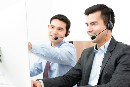 telemarketing: Businessmen wearing headset and looking at computer screen - telemarketing, call center and customer service staff concepts