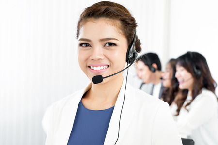 telemarketer: Smiling woman wearing microphone headset as an operator, telemarketer, call center or customer service staff Stock Photo