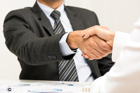 handclasp: Businessman making handshake with a businesswoman in the meeting Stock Photo