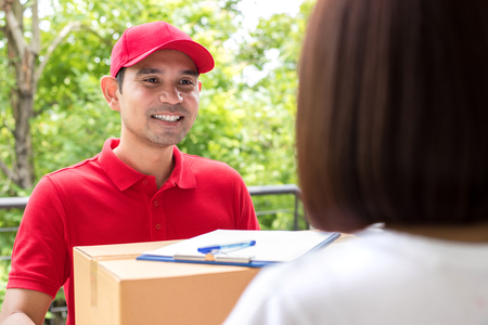 deliverer: Smiling delivery man delivering parcel to a woman Stock Photo