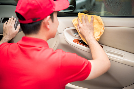 microfiber: A man cleaning car door intetior panel with microfiber cloth - auto cleaning service concept