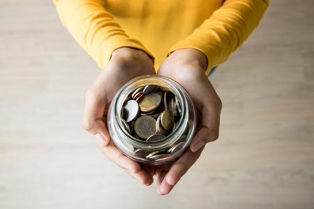 マルチ通貨コイン - トップ ビュー内で若手の女性両手ガラス瓶します。 写真素材