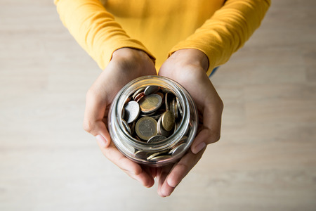 Young woman hands holding glass jar with multi currency coins inside - top view