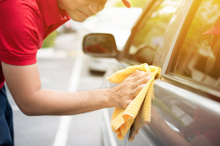 detailing: A man cleaning car with microfiber cloth  - auto cleaning service concept Stock Photo