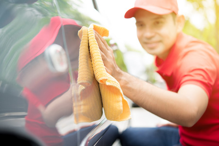 A man cleaning car with microfiber cloth  - auto cleaning service concept Stock Photo