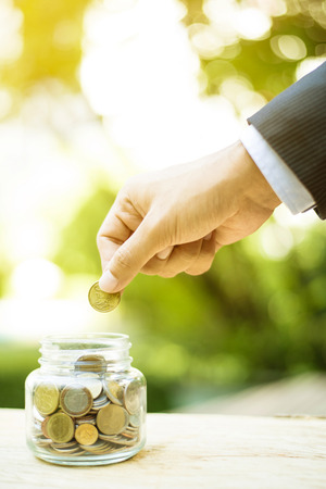 Businessman hand putting money (coin) into the glass jar - savings, investment and donation concepts