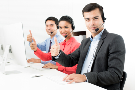 Call center (of telemarketeer) team geven thumbs up Stockfoto