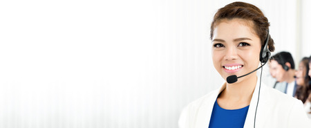 Smiling woman wearing microphone headset as an operator, telemarketer, call center and customer service staff - panoramic background or banner with blank space Stockfoto