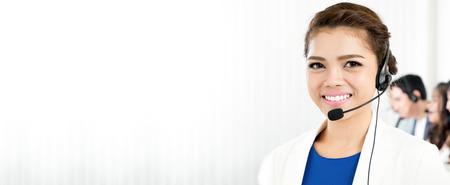 Lachende vrouw draagt headset met microfoon als operator, telemarketeer, call center en customer service medewerkers - panoramisch achtergrond of banner met lege ruimte Stockfoto