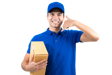 mail me: Smiling handsome delivery man holding box and making call me gesture - isolated on white background