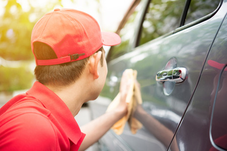 microfiber: A man in red uniform cleaning car   - auto cleaning service concept