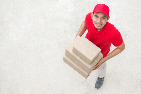 deliverer: Delivery man in red uniform holding parcel box - topview Stock Photo