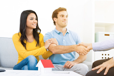 handclasp: Young couple meeting with real estate agent (or financial adviser) at home