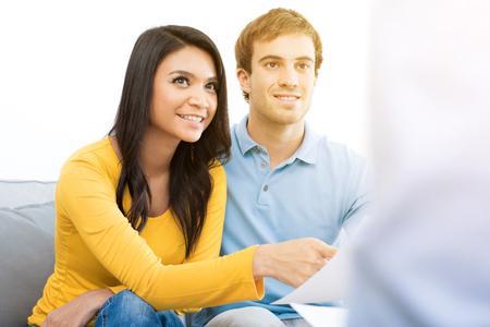Joven pareja reunión de la raza mezclada con el consultor (o consejero, asesor financiero, agente de bienes raíces, etc.) Foto de archivo