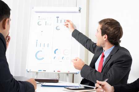 paper board: Young businessman as a meeting leader pointing on the graph Stock Photo