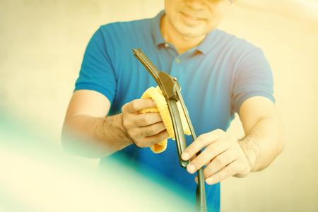 windscreen wiper: A man cleaning car windscreen (windshield) wiper - car detailing and valeting concept