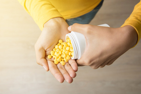 overdose: Woman pouring a lot of pills into her hand - drug addict and overdose concepts Stock Photo