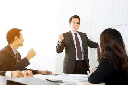 Powerful businessman clenching his fist empowering his colleagues in front of meeting room Stock Photo