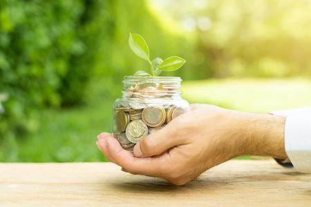 남자 - 비즈니스 및 금융은 유에 의해 개최하는 유리 항아리에 돈 (동전)에서 성장하는 식물