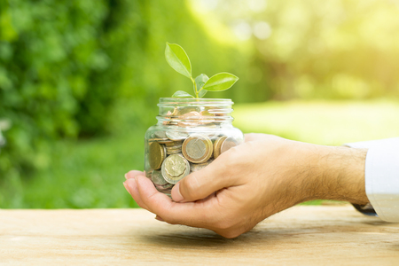 financial metaphor: Plant growing from money (coins) in the glass jar held by a man - business and financial metaphor
