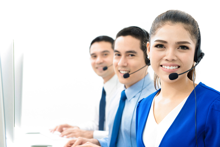 Smiling Asian call center (or telemarketer) team Imagens