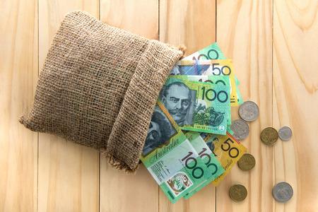 australian money: Money, Australian dollars (AUD), spilled out from a bag