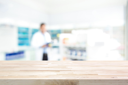 Empty wood counter top on blur pharmacy (chemist shop or drugstore) background