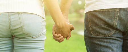 holding hands while walking: Back view of young casual couple holding hands while walking in the park - dating, love and romance concepts