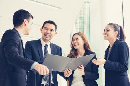 Gelukkige mensen uit het bedrijfsleven bespreken werk in kantoorgebouw corridor, vintage toon effect Stockfoto