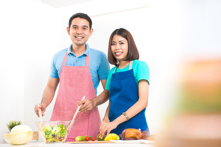 asian wife: Happy Asian couple cooking at home Stock Photo