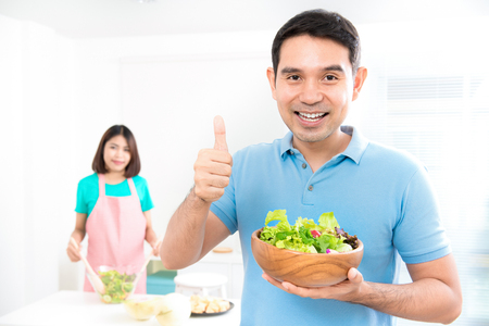 hold on: Asian couple making salad at home