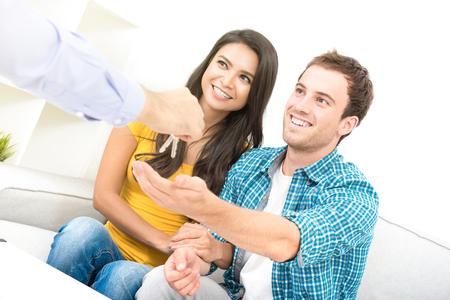 若い異人種間のカップルの不動産業者からキーを受信 - 新しいホームのコンセプトを購入