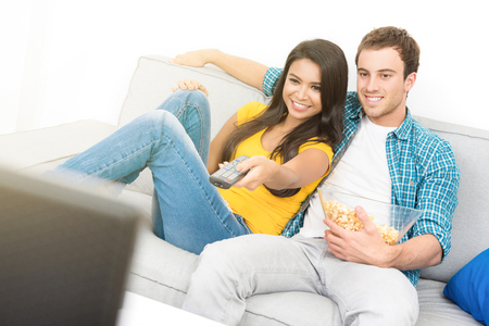 Young happy interracial couple watching TV on the couch in living room