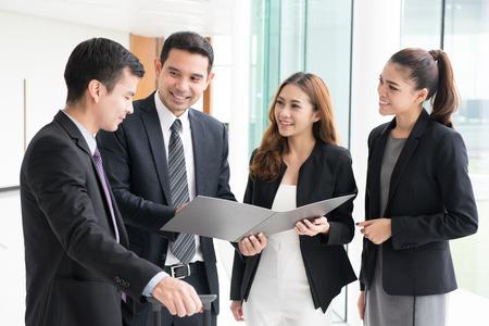 Group of business people discussing work in building corridor 写真素材